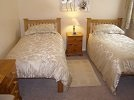A view of the large twin bedded bedroom with quality single beds and pine furniture